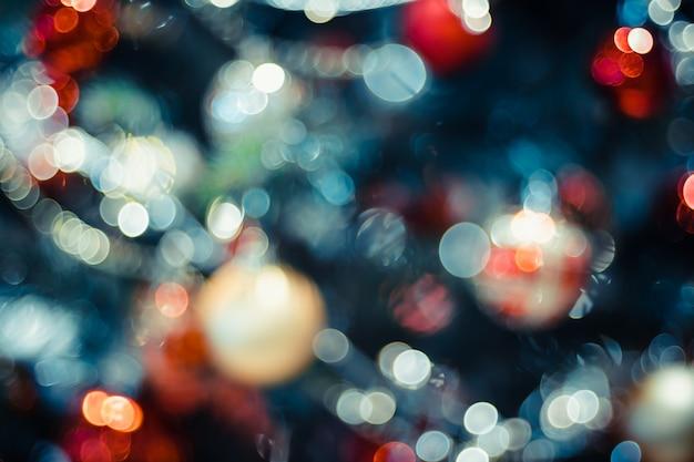 Unscharfe zusammensetzung mit deecorationbällen und hellen schnüren auf weihnachtsbaum mit bokeh licht