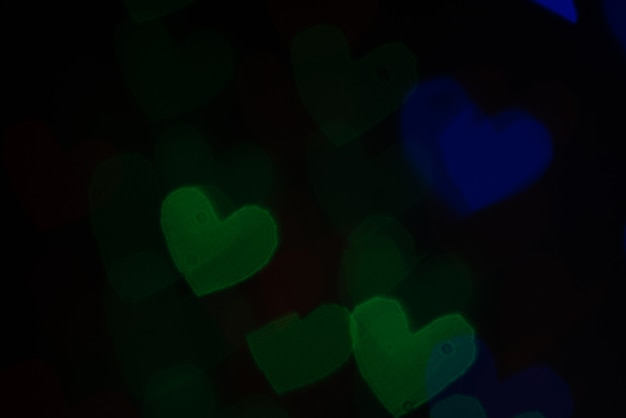 Unscharfer abstrakter herzselektivfokus dunkler hintergrund. valentinstag konzept