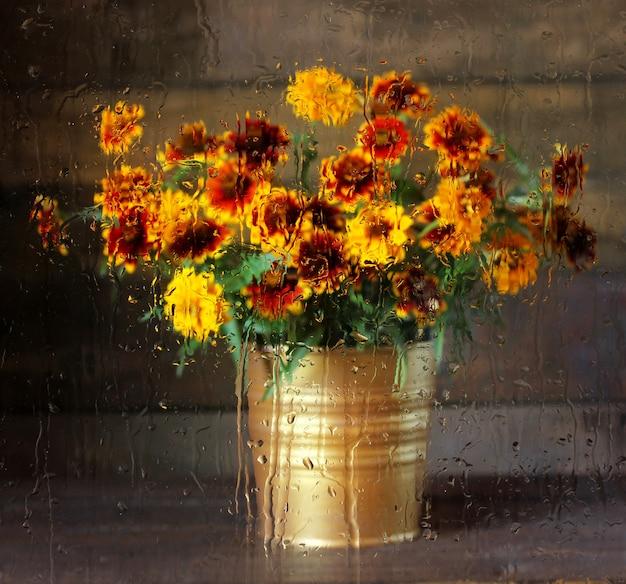 Unscharfer blumenstrauß von herbstblumen hinter dem glas mit regentropfen