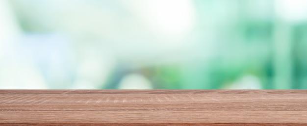 Unscharfer botanischer gartenarbeithintergrund des äußeren hauses mit hölzerner schreibtischtischplatte
