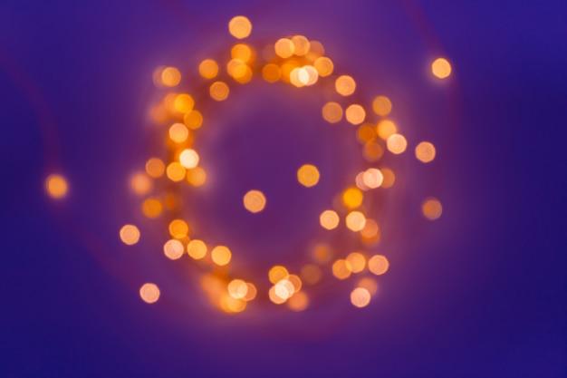 Unscharfer defocused magischer lichterkettenfunkeln durch weihnachtslichter auf blau