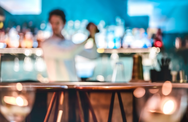 Unscharfer defocused modebarmann, der cocktail an der speakeasy retro- bar auf glücklicher stunde rüttelt