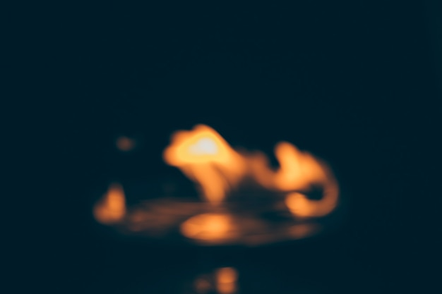 Unscharfer dunkler hintergrund mit brennender flamme