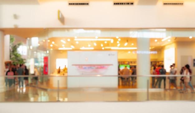 Unscharfer einkaufszentrumhintergrund. menschen zu fuß und im urlaub einkaufen