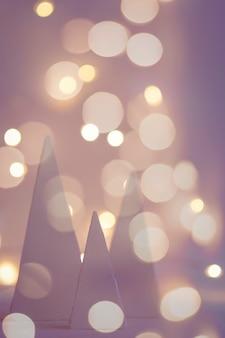 Unscharfer feiertagshintergrund mit weihnachtsbäumen und bokeh-girlandenlichtern