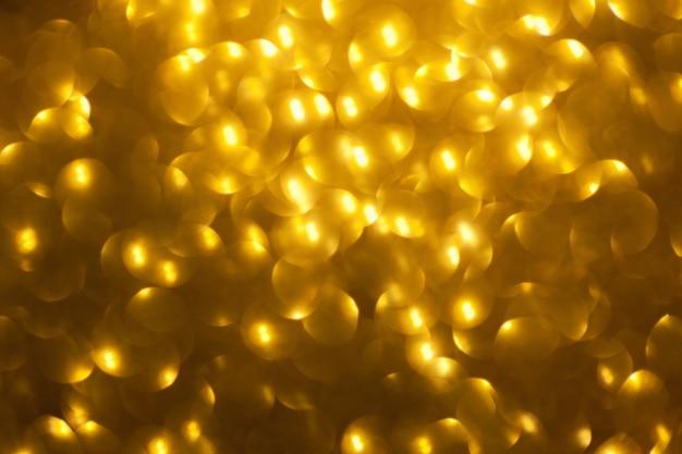 Unscharfer glänzender goldener hintergrund mit funkelnden lichtern,