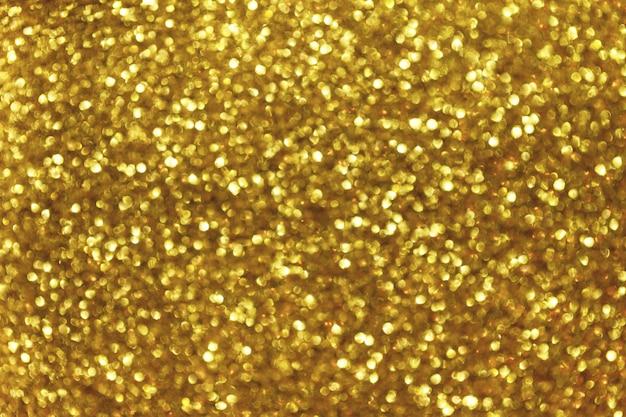 Unscharfer glänzender goldener hintergrund mit funkelnden lichtern.