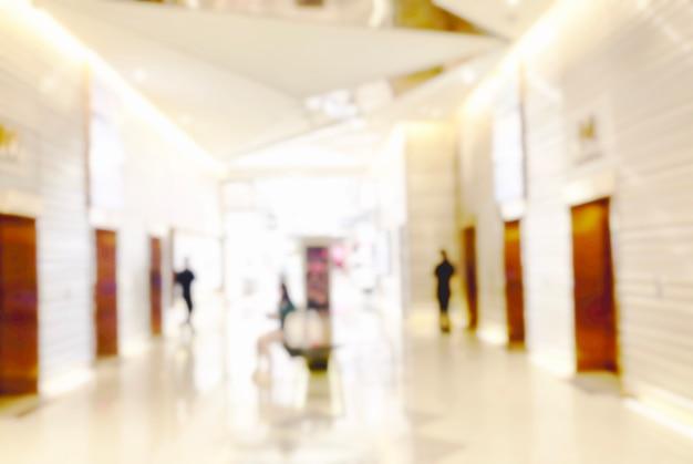Unscharfer heller hintergrund im geschäft im einkaufszentrum für geschäftshintergrund, verschwommenes abstraktes bokeh im innenflur.