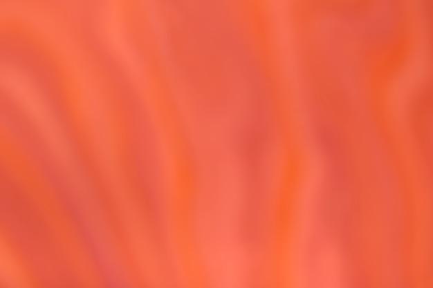 Unscharfer hellorange und roter hintergrund mit gewelltem lockigem muster. defokussierte kunst abstrakter ingwer-gradientenhintergrund mit unschärfe und bokeh. seidentextil.