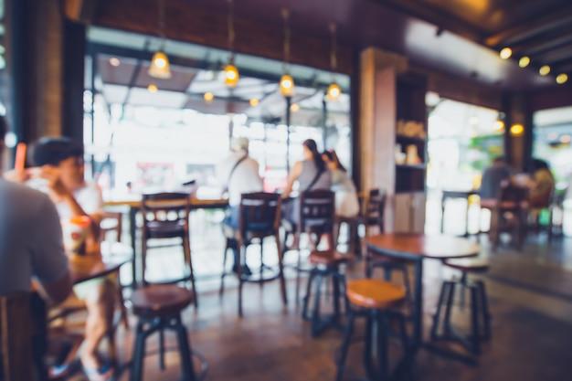 Unscharfer hintergrund der kaffeestube. abstrakter unschärfehintergrund mit leuten im café. vintage farbtonart