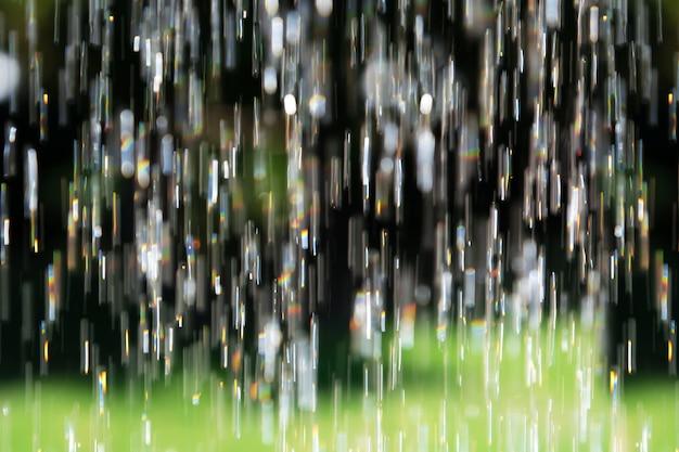 Unscharfer hintergrund, der vertikal wasser mit reflektierender sonne gießt, hebt im garten hervor.