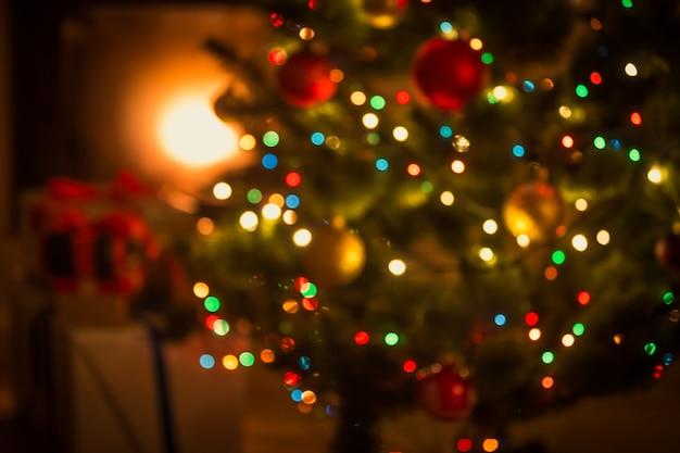 Unscharfer hintergrund des verzierten leuchtenden weihnachtsbaums und des kamins