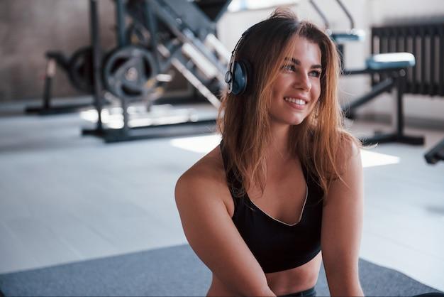 Unscharfer hintergrund. foto der herrlichen blonden frau im fitnessstudio zu ihrer wochenendzeit