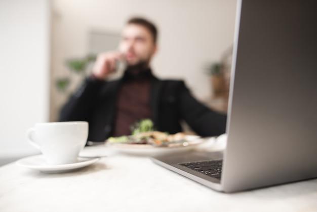 Unscharfer hintergrund. geschäftsmann arbeitet an einem laptop, isst und trinkt kaffee. arbeite in einem cafe