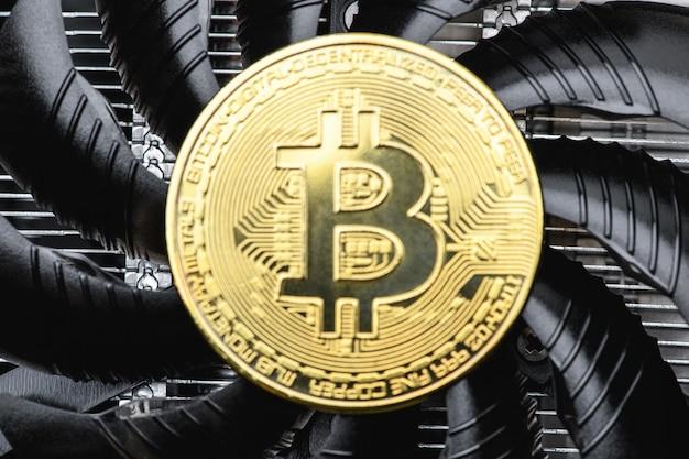Unscharfer hintergrund. gold-bitcoin-münze auf einer schwarzen grafikkarte, ein fan, nahaufnahme. kryptowährung. bitcoin-mining-konzept.