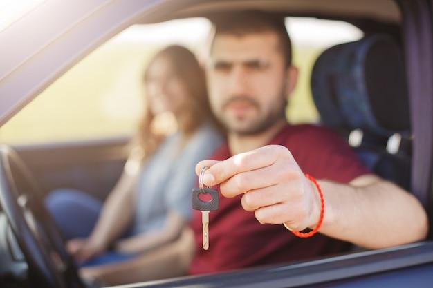 Unscharfer hintergrund. mann hält schlüssel vom fahrzeug, verkauft sein auto