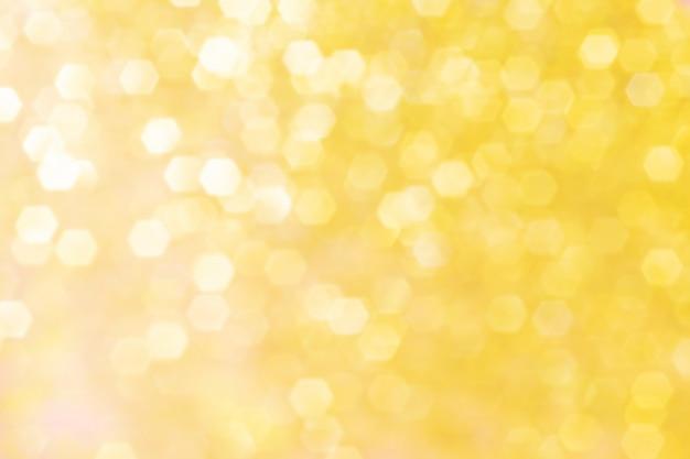 Unscharfer hintergrund mit goldenen scheinen.