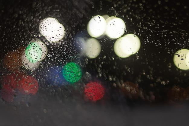 Unscharfer hintergrund mit regentropfen und lichtern.