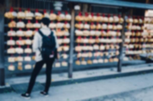 Unscharfer hintergrund. verschwommene frau, die im shintoistischen tempel wartet.