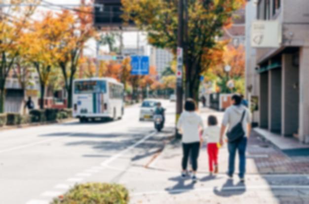 Unscharfer hintergrund. verschwommener japanischer familienspaziergang auf einer stadtstraße.