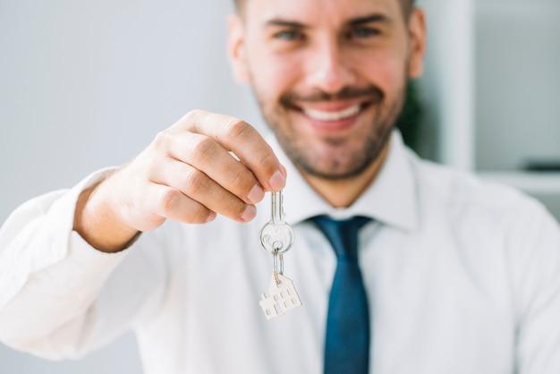 Unscharfer immobilienmakler, der schlüssel hält