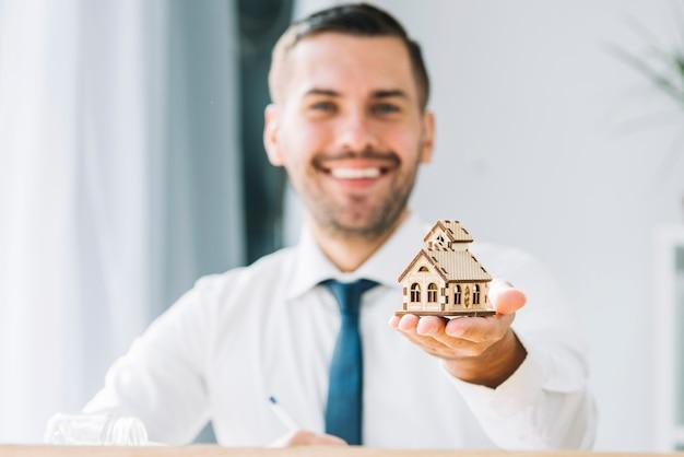Unscharfer immobilienmakler, der spielzeughaus hält