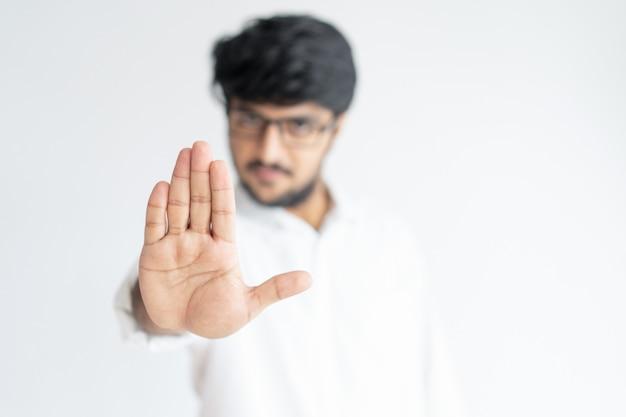 Unscharfer indischer mann, der offene palme zeigt oder geste stoppen