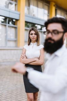 Unscharfer junger geschäftsmann, der zeit auf armbanduhr mit überzeugter geschäftsfrau im hintergrund überprüft