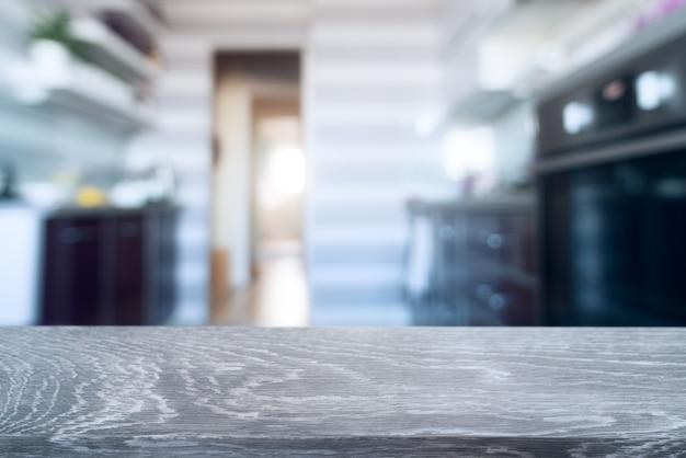 Unscharfer küchenhintergrund mit grauem hölzernem schreibtisch