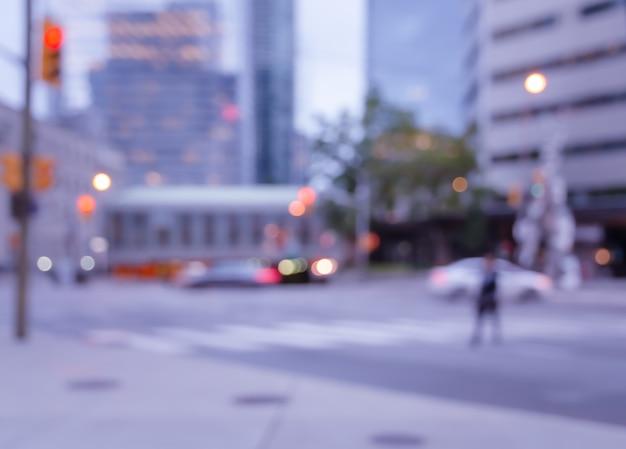 Unscharfer mann, der auf fußgängerüberquerung der straße in der stadt mit bokeh hellem hintergrund geht