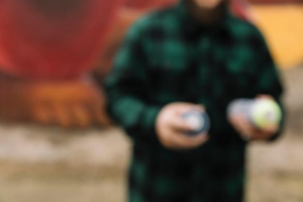 Unscharfer mann, der in der hand aerosolspraydose hält