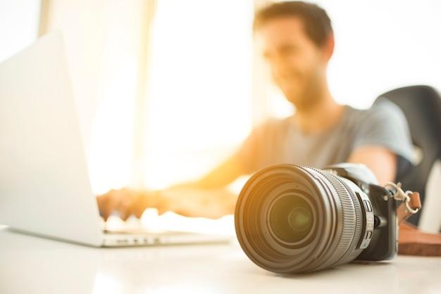 Unscharfer mann, der laptop hinter dslr kamera auf schreibtisch verwendet