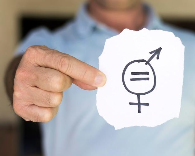 Unscharfer mann, der papier mit geschlechtssymbolen hält