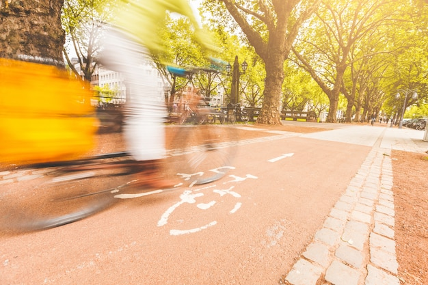 Unscharfer mitfahrer, der auf radweg in düsseldorf radfährt