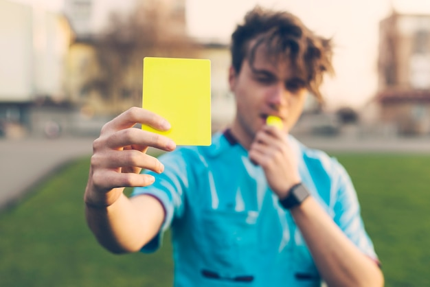 Unscharfer referent, der gelbe karte zeigt
