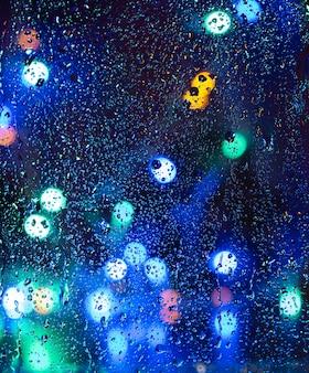 Unscharfer regen fällt nachts ins fenster