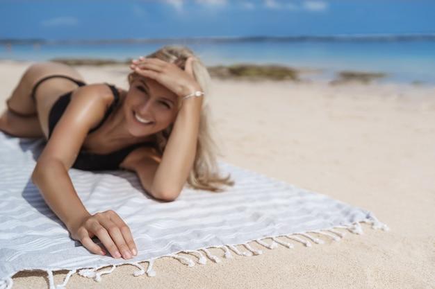 Unscharfer schuss charmante blonde frau schwarzer bikini, der glücklich lächelt.