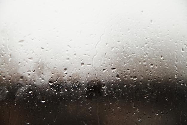 Unscharfer tropfenhintergrund. regnerisches fenster mit fingerabdrücken.
