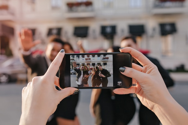 Unscharfes außenporträt von frauen und jungen, die vor dem gebäude vor der party mit dem smartphone im fokus aufwerfen