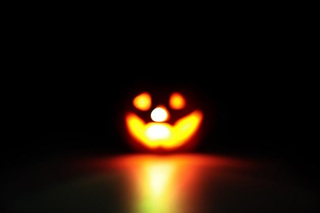 Unscharfes bild des halloween-kürbises auf schwarzem mit dunklem filter