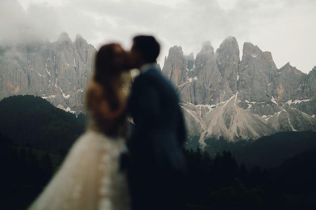 Unscharfes bild des küssens der hochzeitspaare, die vor herrlicher berglandschaft stehen