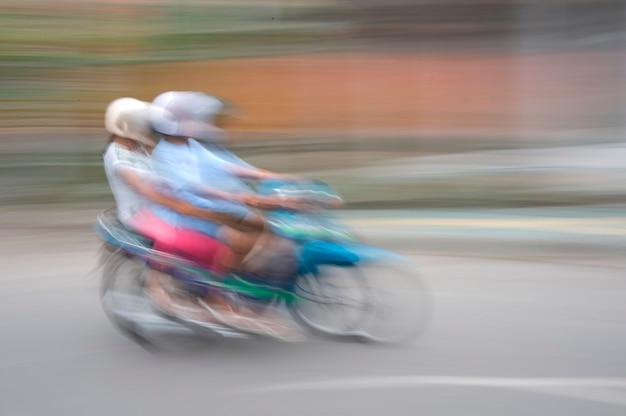 Unscharfes bild von den leuten, die ein motorrad in bali reiten