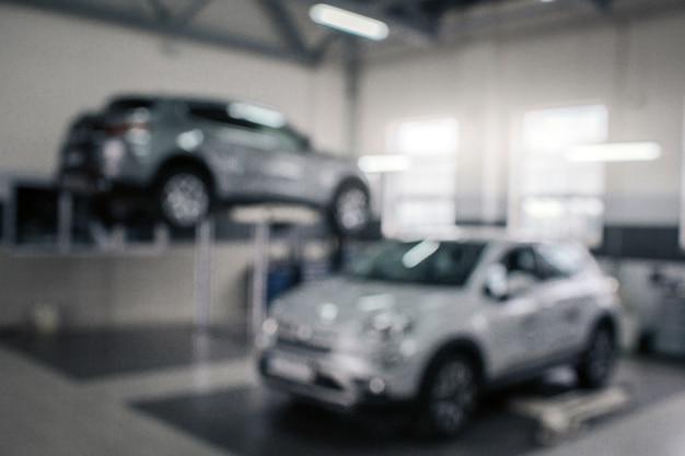 Unscharfes bild von zwei grauen autos im salon. fahrzeug links auf plattform stehen. sie leuchten und funkeln.