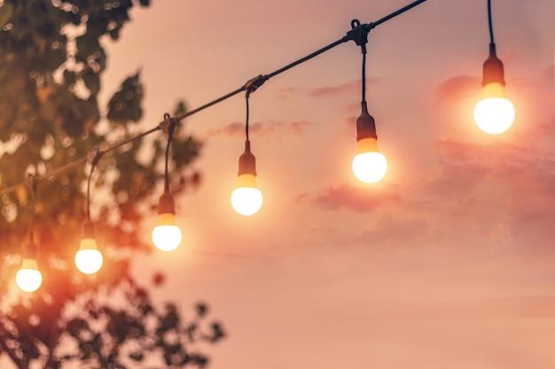 Unscharfes bokeh licht auf sonnenuntergang mit gelber schnur beleuchtet dekor im strandrestaurant