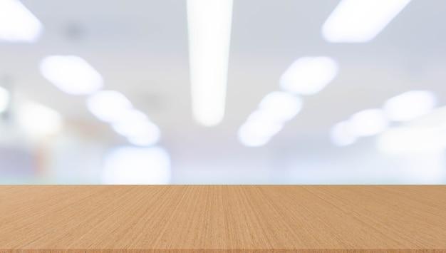 Unscharfes büro mit moderner holztischperspektive für hintergrunddesign-anzeigenkonzept