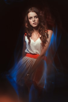 Unscharfes farbkunstporträt eines mädchens auf einer dunkelheit