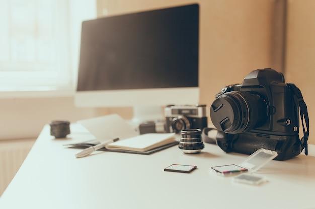 Unscharfes foto des arbeitsplatzes mit kamera und speicherkarten im vordergrund. moderner computer steht auf weißem tisch mit daneben liegendem notizbuch und stift.