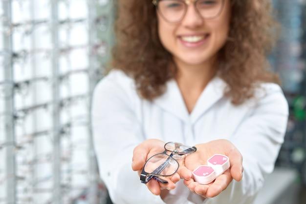 Unscharfes foto des lächelnden okulisten helfend, gläser zu wählen.
