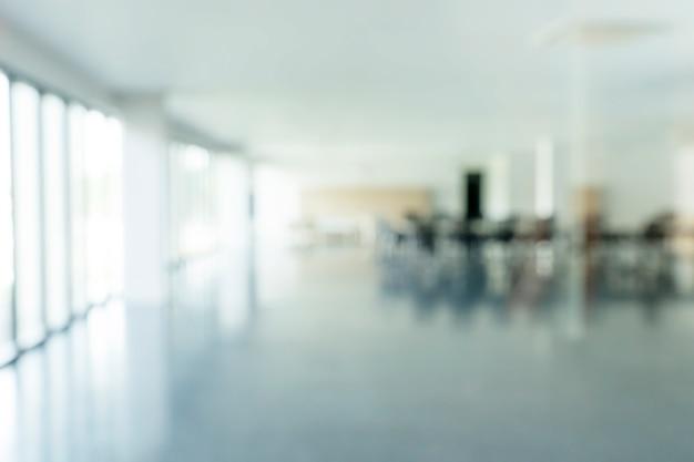 Unscharfes foto des leeren raumes oder des büros mit sonnenlicht vom fenster. abstrakter hintergrund.
