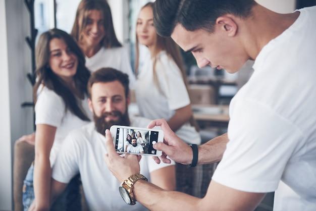 Unscharfes porträt der glückseligen jungen besten freunde mit den händen, die telefon auf vordergrund halten.